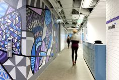 Wunderman / Bienalto Sydney Activity Based Workplace (ABW). Grafitti art by Beatman and Numskull. Reception / arrival / lockers. Polished concrete / white brick / tiles / open ceiling.