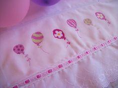 No carrinho ou na hora do banho a toalha fralda, bordada à mão com acabamento em bordado inglês e passa-fita, faz companhia e ajuda a mamãe a proteger o bebê.