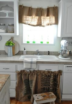 burlap curtains on window and sliders, and inserts for open cabinet fronts. Paint cabinets a greenish color to compliment accent backsplash tiles, and eventually change floor to a beige tile?