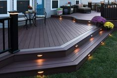 AZEK decking with post cap and and riser lights. A beautiful way to keep your backyard lit at night.