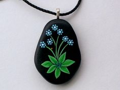 Ready to ship! Small, tender and precious, teal turquoise forget-me-nots with ladybug hand painted on a satin smooth beach stone, the pendant necklace wears comfortably around your neck and stays close to your heart! Hand painted rock is approx. 1-3/4 long x 1-1/4 wide x 1/2 thick, attached to a silver aanraku bail with a powerful epoxy and strung on 20 of black cotton weave cord with a silver claw clasp to be worn as a pendant necklace. Hand painted rock pendant necklace, oo...
