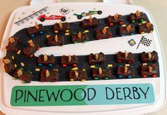 Pinewood Derby Snacks for cub scouts - Fun size snickers with a mini honey teddy graham stuck in..melted chocolate chips to glue a mini m on.  I decorated my cake holder to look like a track that the bears were on...make sure your snickers or candy bars arent too cold...I tried mine out a few days before and I pushed the bear right inside candy no problem..On the day I made these..the bars had gotten cold or hard and they were cracking the bars or breaking the bears..had to precut bear holes