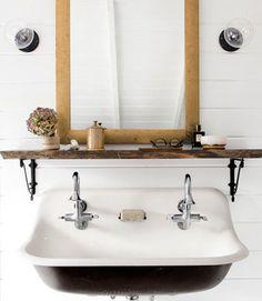 Bathroom Sink - Anthropologie's iron brackets turn a slab of repurposed wood into a shelf in the master bath.