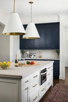 White and gold light pendants hang above a white center island boasting white cabinets adorned with brass hardware and a light gray concrete countertop fixed above a microwave drawer and seating clear acrylic counter stools.