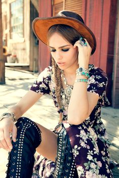 Cute long nineties patterned flower dress black leather knee boots hat braided hair silver accessories.