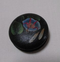 This is a very nice vintage hand painted wood spool or bobbin for ribbon or thread. It is black with a pink/red flower and green leaves on one side and a lily with leaves on the other side. It is an unusual sewing collectible and would be a great addition to anyones sewing tool collection. Measurements: 1 1/4 inch in diameter; 3/4 inch thick. See quarter for size comparison. It is in good condition. Edna's Attic: http://www.etsy.com/shop/grmamoses