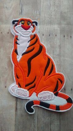 Raja Tiger Patch ~ Aladdin Jasmine Applique ~ No Sew ~ Iron On  Thanks for stopping by The Enchanted Hollow! This listing is for one patch of Raja, Princess Jasmines pet tiger. THE BASIC INFO -  -This Applique measures 7 1/2 x 4 1/2 in the larger size. - Turnaround time can vary from days to weeks. If you have a specific date you need your item by, please let me know so I can accommodate! I try to keep my current turnaround time updated in my shipping and policies section, but if yo...