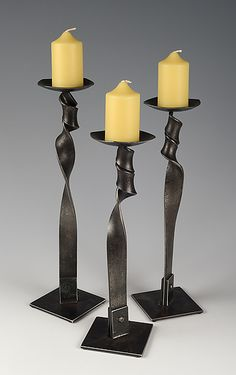 """""""Twist Candle Holder Trio"""" Metal Candleholders by Rob Caperell This set of three candle holders is made by heating recycled flat steel bar, applying an elegant twist, and riveting it to a square base."""