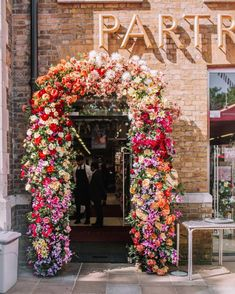 A bright colourful floral arch at Partridges Food to celebrate Chelsea in Bloom and the royal wedding Floral Arch, Arte Floral, Floral Wreath, City Flowers, Wall Backdrops, Flower Aesthetic, Flower Boxes, Floral Wedding, Floral Arrangements
