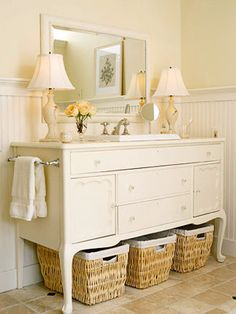 beautiful vanity from old side board - paint, cut out back space for plumbing, put several coats of polyurethane on top, cut out space for sink & faucets using sink & faucet templates, install as per instructions, add towel bar on side, mirror above, and lined wicker baskets below...