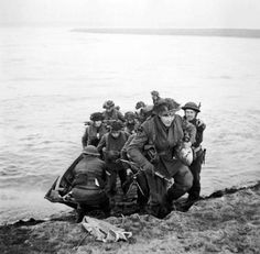 Men of the 15th Scottish Division leave their assault craft after crossing the Rhine and double up the east bank to their assembly point near Xanten.