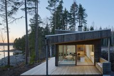 Dive Architects designed this stunner of a house on a lake. There is a Scandinavian feel with this house. All of the Alvar Aalto lighting caught my eye Dive Architects designed this stunner of a house Ideas De Cabina, Sweden House, Roof Shapes, Haus Am See, Wooden Steps, Rural Retreats, Outdoor Seating Areas, Pine Forest, Brick Fireplace