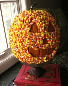 candy-corn decorated pumpkin. You could carve the pumpkin and light it too! How pretty that would be!!!!