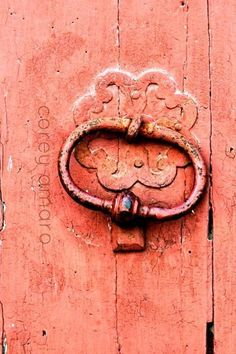 Knocker on a coral pink door.