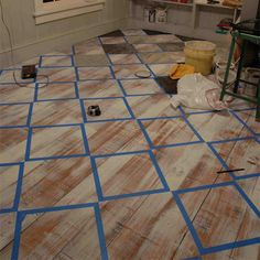 use masking tape to mark out design for painting wooden floor with checkerboard or chevron design