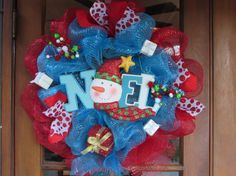 This wreath is smothered in red and turquoise deco mesh adorned with three white glittery presents with silver bows, a red glittery present