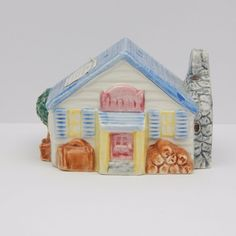 Vintage 1995 pre-owned collectible single salt, pepper or spice shaker.  Designed to look like an Inn building with blue roof and an Inn plaque sign above the door.  The exterior has a pile of firewood, chimney, trees, chair, suitcase. The sticker on the roof indicates this shaker is a hand painted piece and provides cleaning instructions.  . #SaltAndPepperShakes #Fitz&Floyd #Inn