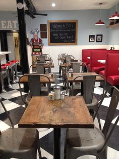 Design interiors at Bill's Luncheonette (billsluncheonette.com).  Red booths with accent walls/wainscoting, black and white tile floors, custom wood shelves, metal cafe chairs, reclaimed wood tabletops, and antique kitchen equipment and knick-knacks.