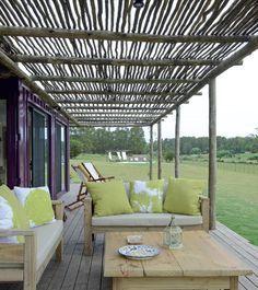 Bajo la pérgola de troncos, un par de camastros y una mesa de pino tratado generan un espacio de descanso para disfrutar de la vista del campo.