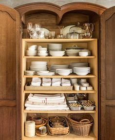 The French armoire in the cookhouse pantry was retrofitted with simple pine shelves to house Kurt's impressive collection of white dinnerware, enamel cutlery, and antique linens.