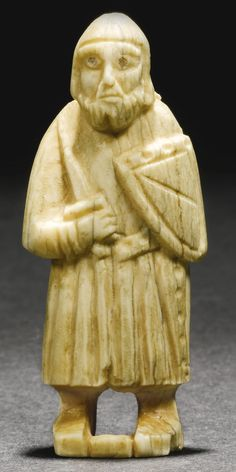 NORTH EUROPEAN, 12TH/ 13TH CENTURY PAWN IN THE FORM OF A STANDING GUARD marine ivory 7.8cm., 3in.