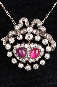 An antique pendant designed as two hearts set with rubies and diamonds, surmounted by a diamond-set bow, mounted in silver and gold, late 19th century. #antique #pendant