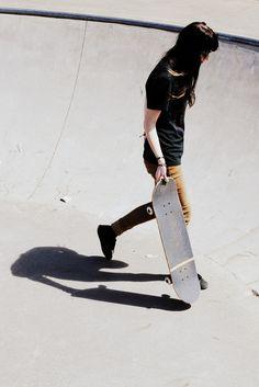skater girl in bowl. weariing simple black tee and tan turn up skinnys. tomboy/femme style