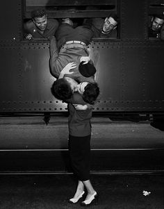 California National Guardsman hanging out window of train, kissing his wife goodbye.
