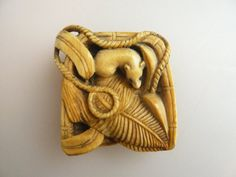 RAT IN A BASKET 19TH CENTURY IVORY NETSUKE — This charming 19th century ivory Netsuke is depicting a rat with inlaid eyes, hiding amidst leaves in a straw scoop. Very well rendered details. Unsigned, early 19th c., length 4.8 cm. Good condition apart from old scratches. From an old collection of about 200 Netsuke built up in the sixties and seventies in Japan. {available for purchase}