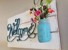 This warm and inviting welcome sign will be the envy of all your friends and family. It measures 30x16x5 and is hung by a wire. This amazing sign can be made to order by choosing the paint for the wood as well as the paint for the jar. The Welcome is a teal color but could be painted as well. The medium used is chalk paint and can be done as a solid or distressed. The wood is reclaimed pallet wood assembled by hand. All color choices, as well if youd like it solid or distressed, should be…