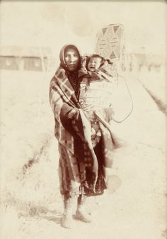 Crow woman, Lives High, holding her baby aloft in a beaded cradle to be blessed by the Sun, c. 1900. The location is the quadrangle at Crow Agency, Montana. The recently planted cottonwood saplings seen in the background are now gnarled and towering trees which shade the Agency grounds. Photograph by Fred E. Miller. Heritage Auctions. September 2009. American Indian Art Auction #6029. ДА.