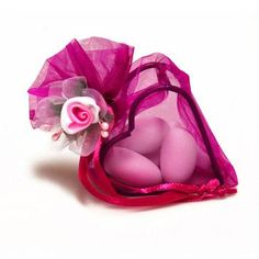 Süßes Gastgeschenk im pinkfarbenen Organzasäckchen mit fünft Hochzeitsmandeln
