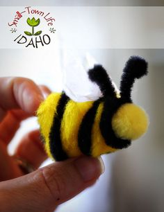 Bees were made from large, yellow poofballs...that's the technical term...wrapped with black pipe cleaner. After tearing tissue paper into the shape I wanted for wings, they were glued on top. Then, the completed bees were arranged and hot-glued to the hive. That's it!