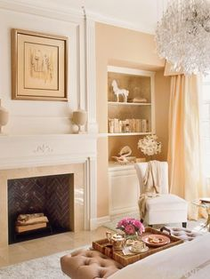 Peaches and cream bedroom. LOVE the chandelier! And look how they decorated the fireplace.
