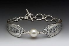 """This elegant silver spoon bracelet features the look of an antique silver pattern and a white Swarovski pearl framed in delicate points. length: 6 1/2"""" - 8"""" adjustable width: 5/8"""" silver plate silver"""