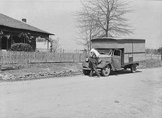 """A """"rolling store"""" salesman carrying sack of flour into rural home. Coffee County, Alabama"""