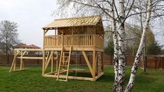 A wooden playground with ladder, climbing wall and a hanging platform to swing