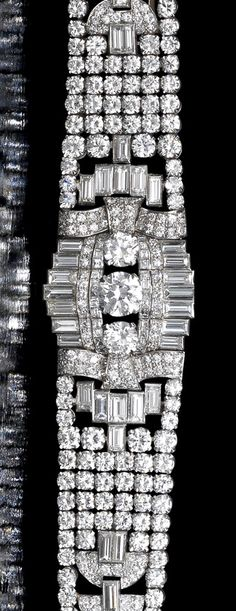 An Art Deco diamond strap bracelet, circa 1935 Set to the centre with three principal brilliant-cut diamonds, between courses of square and single-cut diamonds and within a crenellated border of baguette-cut diamonds, the articulated tapering strap of mesh design interspersed with demi-lune and geometric motifs, composed of brilliant and single-cut diamonds and baguette-cut diamond highlights, remaining diamonds approximately 32.00 carats total, length 17.0cm