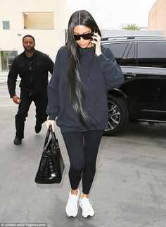 Sleek: She wore her raven tresses down along the sides of her face, matching her black leather purse and sunglasses