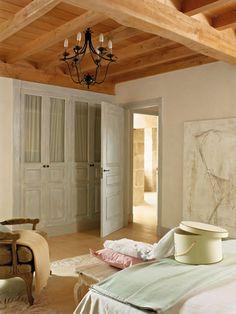 Dormitorio rústico con armarios de madera clara con cortinas en el interior_00315226