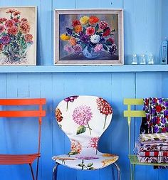 colourful chairs and beautiful floral paintings with a blue backdrop, who says it all has to match?
