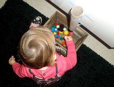 Jouer avec des pompons et un tube cartonné (activité Montessori).