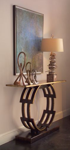 "Add jewelry to your space with the John-Richard Bracelet table. Finished in Windsor black with aged gilt accents, this console is a series of interlocking curved rails atop an American walnut base. The top is aged gilt. Continuing the circular theme, metallic sculptures and the Stacked lamp  rest before ""Aura"" by Anne B. Schwartz. All the crystalline textures & subtle iridescent hues have been rebuilt by hand."