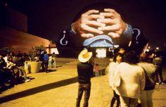 Krzysztof Wodiczko | El Centro Cultural Projection (Part I) Proyección de una fotografía sobre el Centro Cultural de Tijuana. El tema de la proyección son los trabajadores mejicanos indocumentados que arriesgan sus vidas para cruzar a los Estados Unidos en la búsqueda de trabajo. La imagen usada en la proyección muestra a un trabajador mejicano con sus manos detrás de su cabeza apunto de ser detenido.