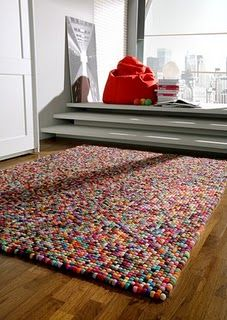 Felted ball rug. Could DIY it (tutorial here: http://www.deepfriedkudzu.com/2006/05/easy-felt-balls.html).