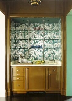Katie Ridder wet bar in house in Arkansas. Glass and nickel shelving against that silver-on-peacock Japanese Floral wallpaper by Florence Broadhurst