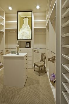 Large white walk in closet fitted with built in modular shelves boasts a custom lit, black framed, glass, wedding dress display case mounted over a built in dresser and flanked by stainless steel clothing rails illuminated by recessed lighting. Wedding Dress Display, Wedding Dress Storage, Wedding Dress In Frame, Wedding Dress Shadow Box, Smart Closet, Diy Walk In Closet, Vanity In Closet, Dresser In Closet, Closet Mirror