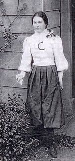 """4'10"""" Sarah DeForest Hanscom shows off the 1896 Cal women's basketball uniform, with """"UC"""" on the front in blue and gold"""