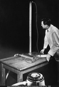 Vacuum cleaners, 1954  Vacuum cleaners' suction ability is tested by forcing air through the vacuum cylinder as the tester reads the measuring gauge.