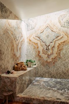 Bookmatched stonework dominates the master shower, which Bacon has softened up with plants and natural sea sponges.